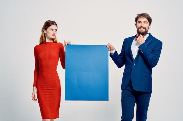 Mann und frau, die blauen mockupplakatwerbungskopienraum halten