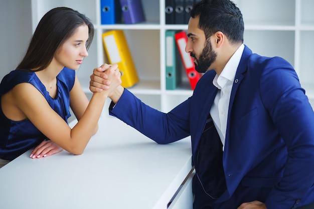 Mann und frau, die das armdrücken im büro tun