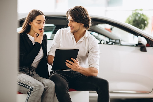 Mann und frau, die ein auto in einem autosalon wählen