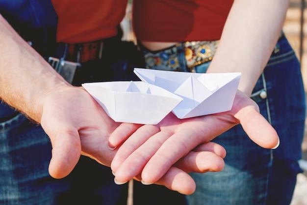 Mann und frau, die ein paar papierschiffe auf palmenhänden halten. paar mit symbol der liebe und zusammengehörigkeit.