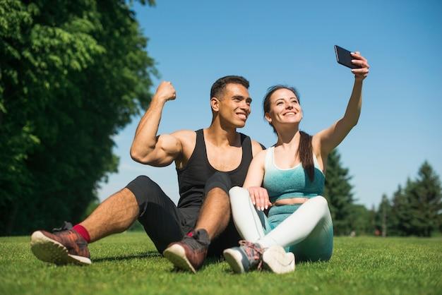 Mann und frau, die ein selfie in einem park nehmen