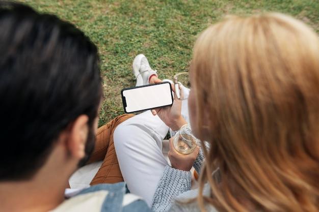 Mann und frau, die ein telefon beim picknick betrachten
