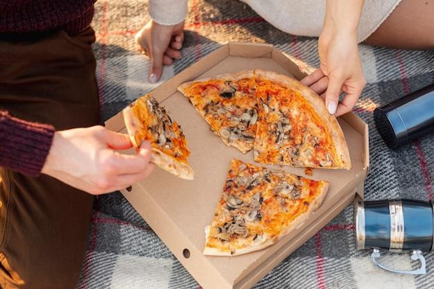 Mann und frau, die eine pizza draußen essen
