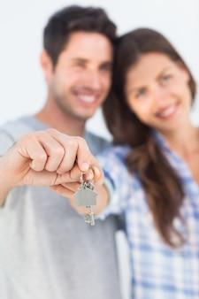 Mann und frau, die einen schlüssel mit einem haus keychain darstellen