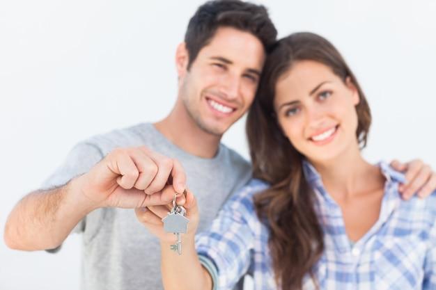 Mann und frau, die einen schlüssel mit einem haus keychain halten