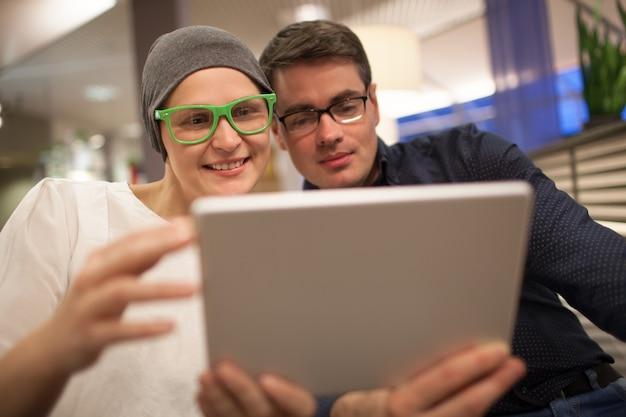 Mann und frau, die elektronische tablette im restaurant verwenden