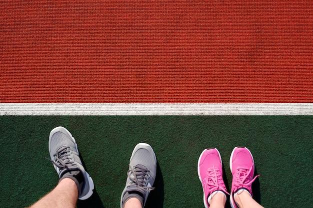 Mann und frau, die für lauf bei stadiim bahn sich vorbereiten. füße in turnschuhen zum joggen draufsicht.