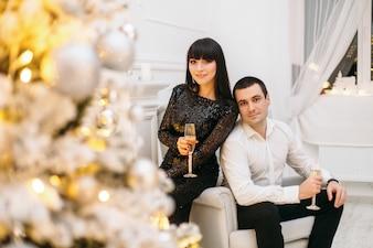 Mann und Frau, die für ein festliches Abendessen gekleidet werden, stehen vor einem glänzenden Weihnachtsbaum