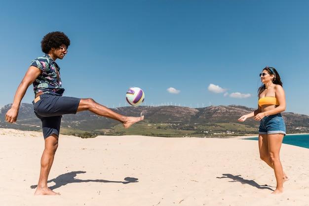 Mann und frau, die fußball auf sandstrand spielen