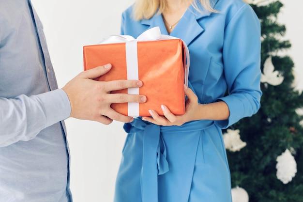Mann und frau, die geschenkbox halten. feiern sie ein frohes neues jahr oder weihnachten