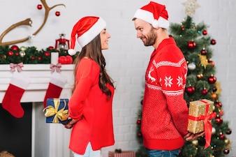 Mann und Frau, die Geschenke von den Rückseiten halten