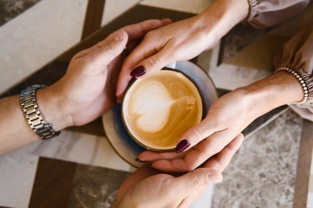 Mann und frau, die hände auf einer kaffeetasse halten