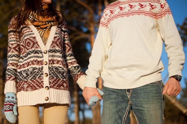 Mann und frau, die hände in winterpullovern auf der oberfläche von kiefern halten