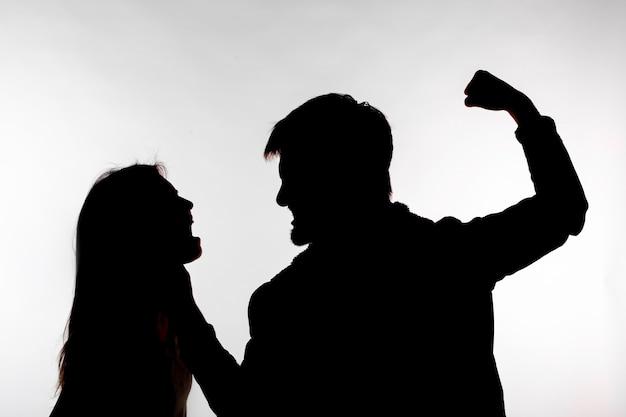 Mann und frau, die häusliche gewalt in der studio-silhouette ausdrücken