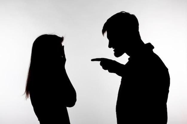 Mann und frau, die häusliche gewalt in studio-schattenbild lokalisiert auf weißem hintergrund ausdrücken.