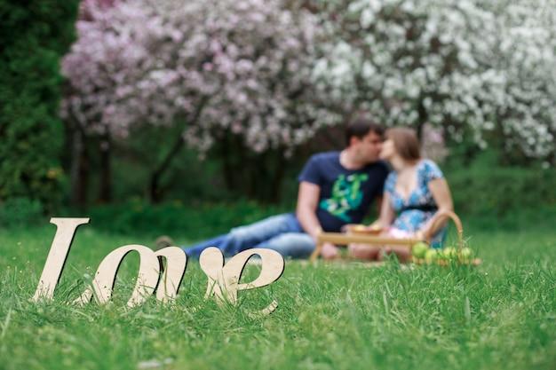 Mann und frau, die im blütenpark am sonnigen tag ruhen. paar verliebt hugg und küssen auf die natur auf blühenden bäumen wand. romantisches date im frühlingsgarten im freien. wort liebe auf grünem gras