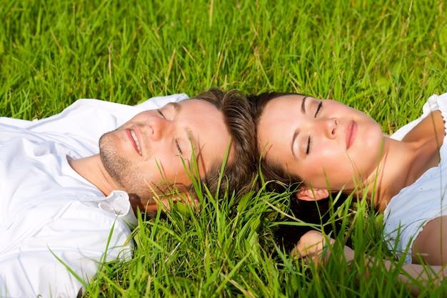 Mann und frau, die in das gras auf einer wiese legen