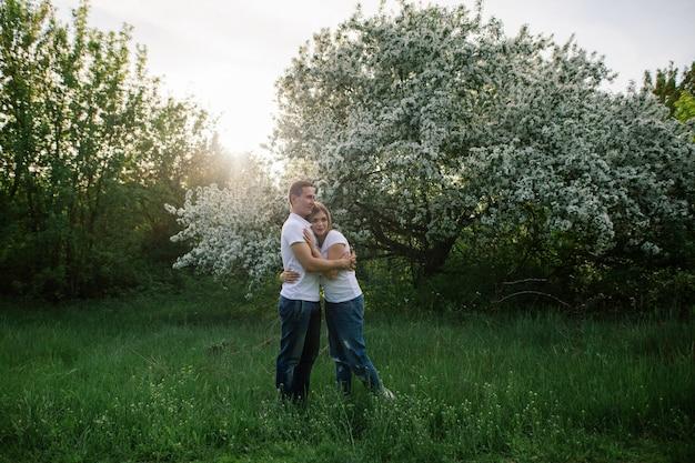 Mann und frau, die in einem grünen park am sonnigen tag stillstehen glücklicher kerl und mädchen umarmen und küssen in der natur. liebesgeschichtekonzept liebespaar nahe blühenden bäumen garten des romantischen datums im frühjahr draußen.