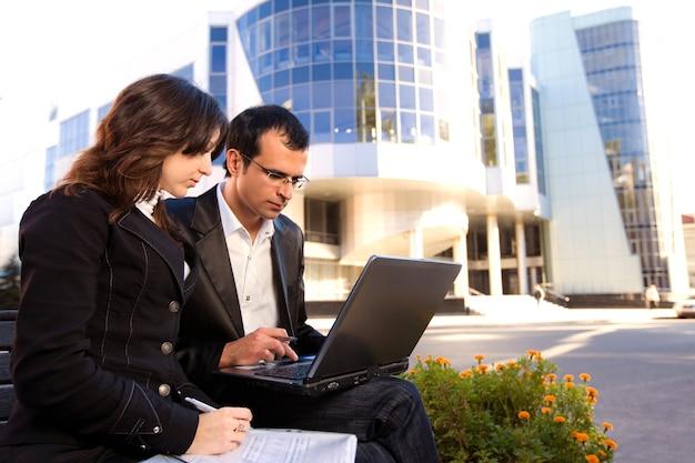 Mann und frau, die laptop-bildschirm betrachten und auf bank vor bürogebäude in sonnigem wetter sitzen