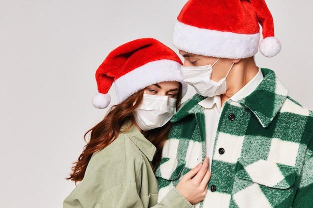 Mann und frau, die medizinische masken tragen, umarmen urlaub