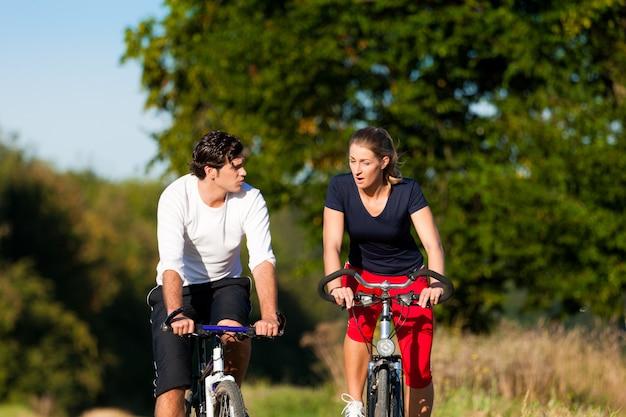Mann und frau, die mit fahrrad trainieren