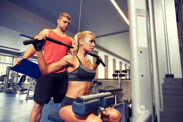 Mann und frau, die muskeln auf turnhallenmaschine biegen