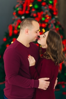 Mann und frau, die nahe dem weihnachtsbaum stehen