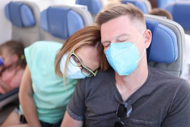Mann und frau, die schutzmasken tragen, fliegen im flugzeug