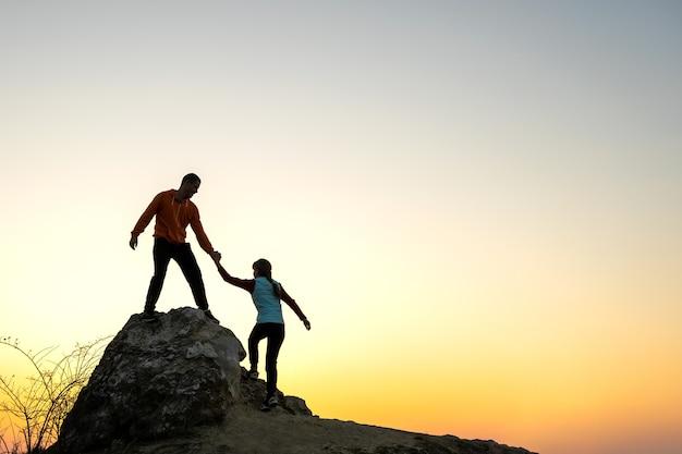 Mann und frau, die sich gegenseitig helfen, bei sonnenuntergang in den bergen einen großen stein zu erklimmen. paar klettert auf einem hohen felsen in der abendnatur. tourismus, reisen und gesundes lifestyle-konzept.