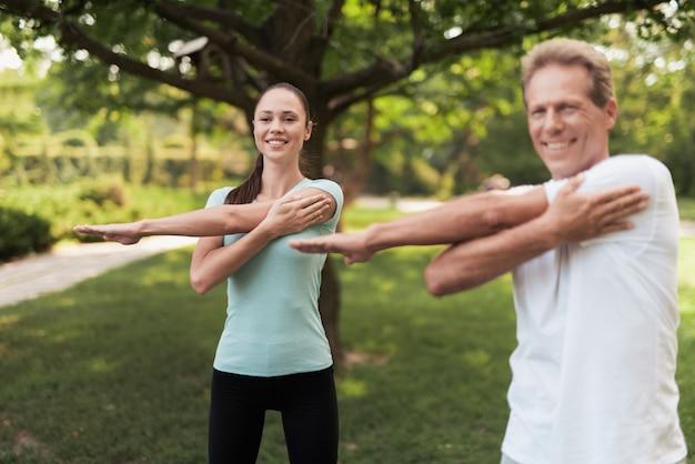 Mann und frau, die übungen im park machen sie wärmen sich auf