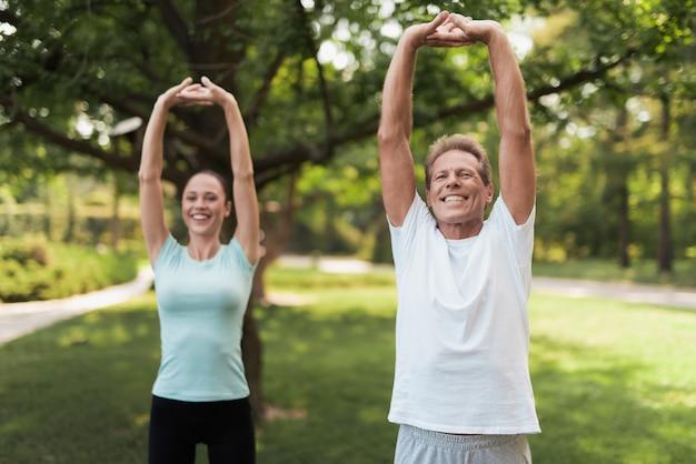 Mann und frau, die übungen im park tun.