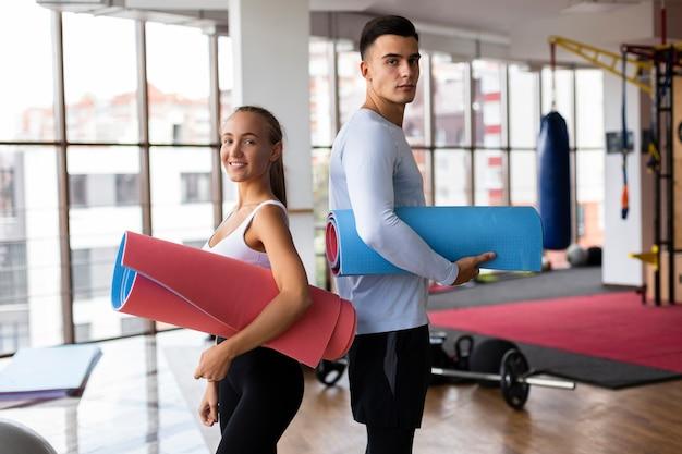 Mann und frau, die yogamatten halten