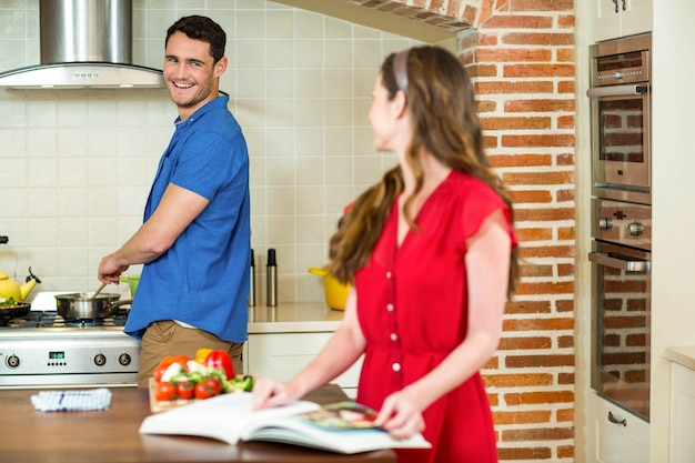 Mann und frau, die zusammen beim in der küche zu hause arbeiten sprechen