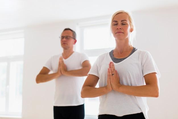 Mann und frau, die zusammen yoga machen