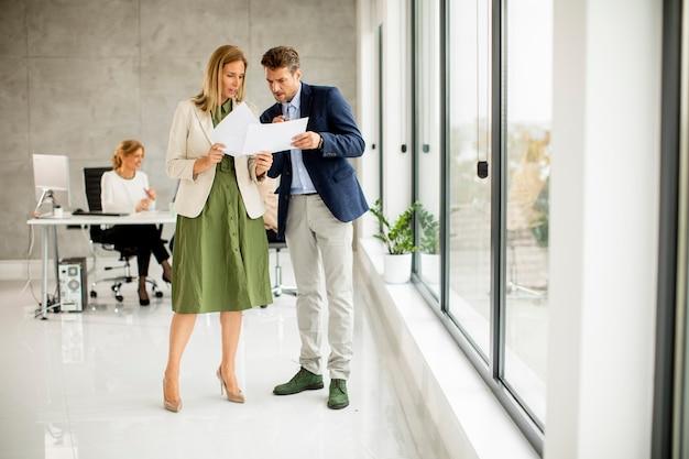 Mann und frau diskutieren mit papier in händen drinnen im büro mit jungen leuten, die hinter ihnen arbeiten