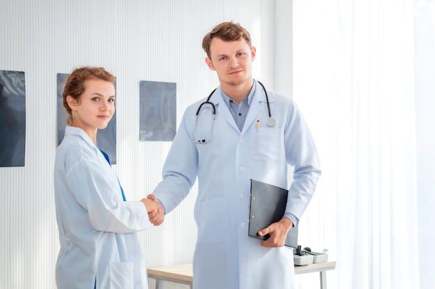 Mann und frau doktor am krankenhauszimmer, das einen händedruck gibt.