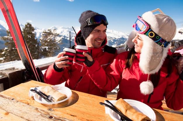 Mann und frau entspannen sich nach dem skifahren und haben spaß im skigebiet