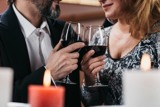 Mann und frau erhöhen gläser mit rotweinabschluß oben