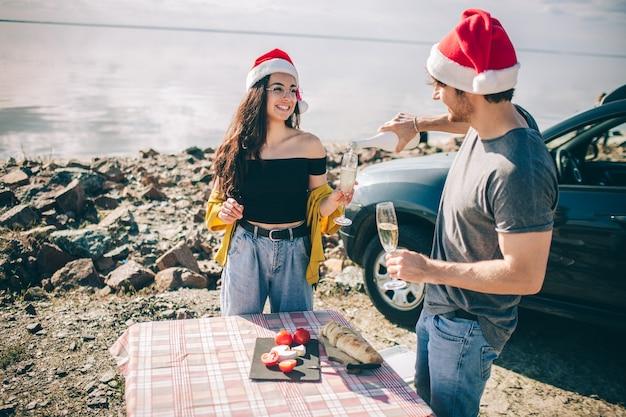 Mann und frau feiern weihnachten, während champagner nahe wasser trinken