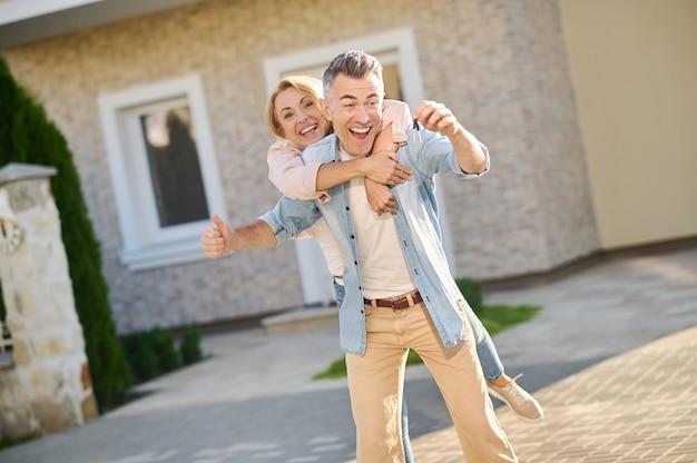 Mann und frau freuen sich über schlüssel zum neuen zuhause
