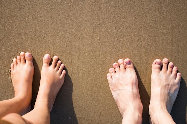 Mann und frau füße am sandigen braunen strand.