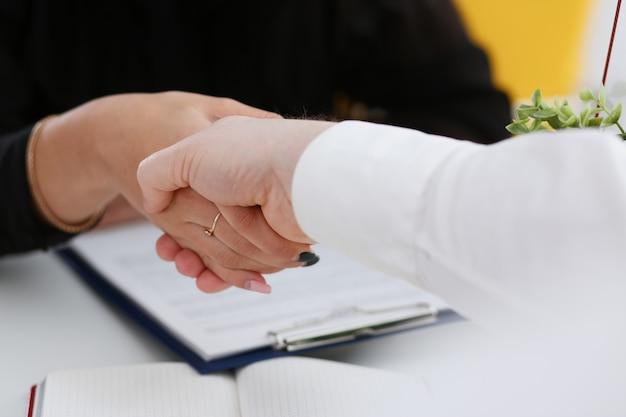 Mann und frau geben sich im büro die hand als hallo