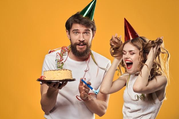 Mann und frau geburtstag festlichen kuchen gelben hintergrund