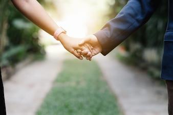 Mann und Frau gehen und halten seine Hand