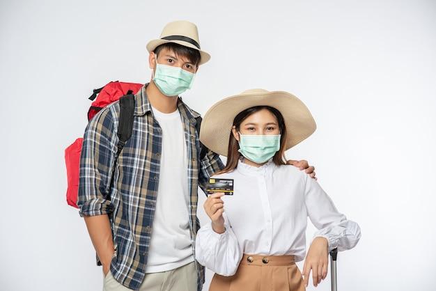 Mann und frau gekleidet, um zu reisen, masken zusammen mit gepäck tragend