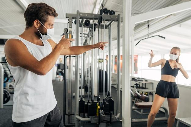 Mann und frau grüßen sich im fitnessstudio