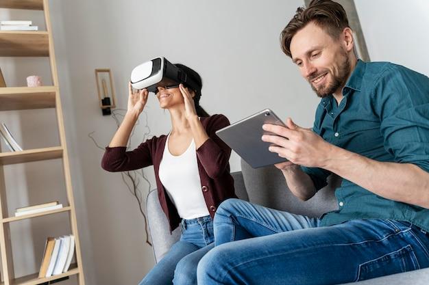 Mann und frau haben spaß zu hause mit virtual-reality-headset und tablet