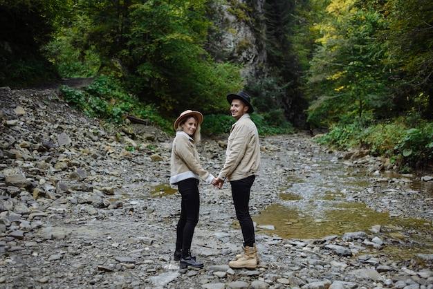 Mann und frau halten hände in der nähe eines gebirgsbaches. lustige ferien inmitten von bergen und wäldern