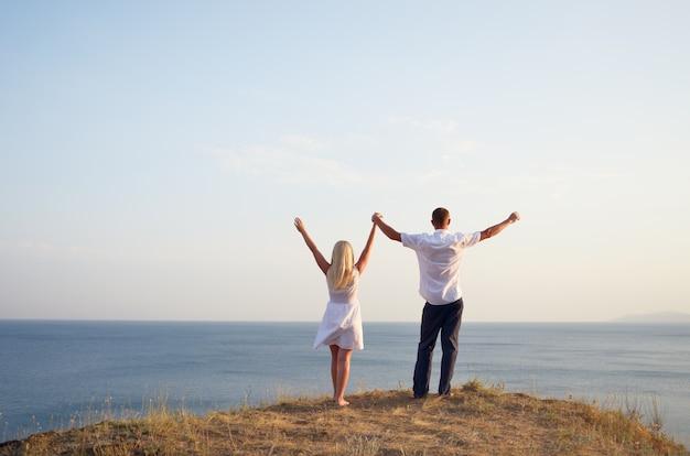 Mann und frau heben ihre hände zum himmel, während sie am strand stehen