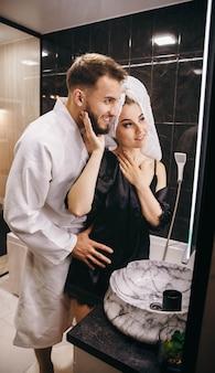 Mann und frau im badezimmer spielen vor dem spiegel herum
